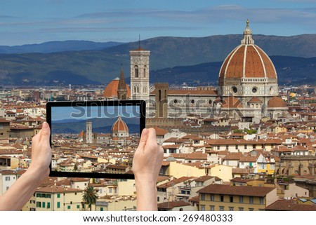 In the bottom left of the photo are hands holding tablet, with photo of the Cathedral Santa Maria del Fiore in Florencel. Background of the photo contains the photo of Florence (Tuscany, Italy) - stock photo