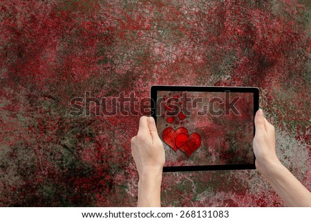 In the bottom right of the photo are hands holding tablet, whose screen contains photo of the grunge texture background with the red hearts. Background of the photo is  the same grunge texture - stock photo