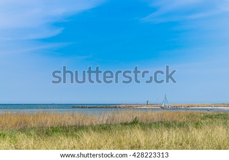In the dunes of the Baltic Sea with sail ships in the background, Germany - stock photo