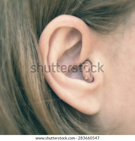 In-the-ear hearing aid in close-up - stock photo