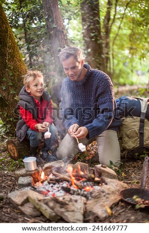 in the evening a father and his young son roasting marshmallows on a campfire in the woods, their backpack  behind them - stock photo
