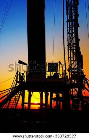 In the evening, the silhouette of oilfield derrick - stock photo