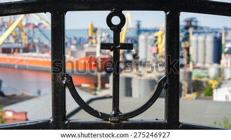 In the foreground can be seen an anchor in an iron fence. Back blurred the background you can see sea trade port and the orange ship. - stock photo