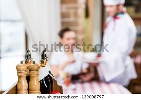 in the foreground stand with salt and pepper and cook in the background serves pretty woman - stock photo