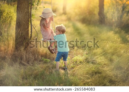 in the forest in sunny sunshine swing ride boy with girl - stock photo