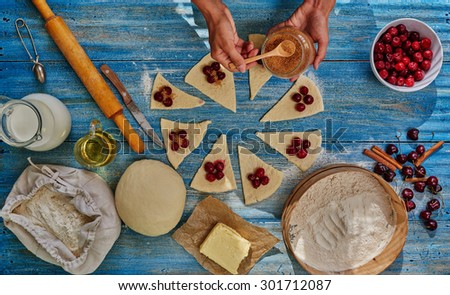 In the frame of female hands gently fold cherry filling over the dough and sprinkle with sugar - stock photo