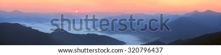 In the highlands of Ukrainian Carpathians growing beautiful grass in background the highest peaks Svidovets, autumn sun illuminates its golden rays of the early morning and in the evening at sunset - stock photo