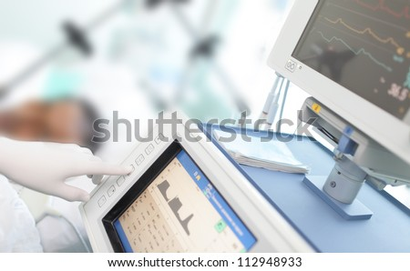 In the ICU. Doctor changes the parameters artificial lung ventilation near the bedside. - stock photo