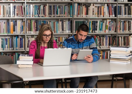In The Library - Handsome Two College Students With Laptop And Books Working In A High School - University Library - Shallow Depth Of Field - stock photo