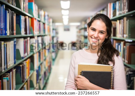 In the library - pretty female student with books working in a high school library. - stock photo