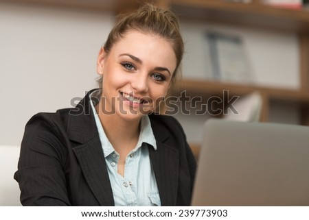 In The Library - Pretty Female Student With Laptop And Books Working In A High School Or University Library - Shallow Depth Of Field - stock photo