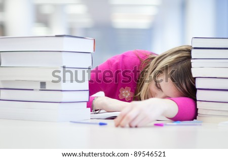 in the library - very tired/exhausted, pretty, female student with books working in a high school library (color toned image) - stock photo
