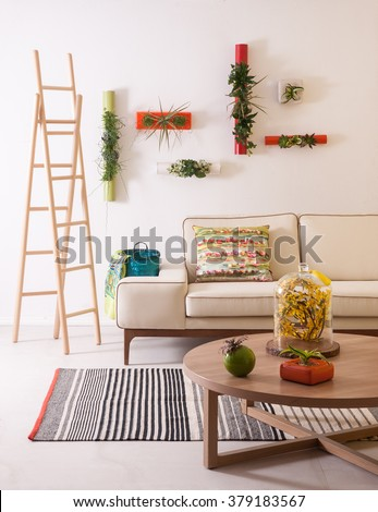 In the modern living room with comfortable sofas, natural wood staircase, flowering of modern wall decor - stock photo