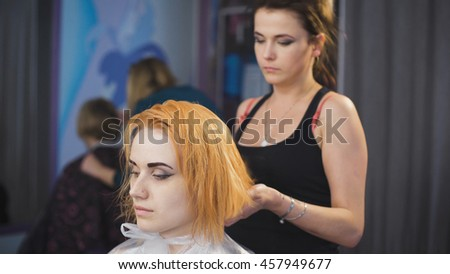 In the professional salon hairstyle on the girl's head dried hairdryer. After staining and washing hair. The girl in a black dress with blond hair - stock photo