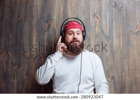 In the rhythm of my music. Relaxed young bearded man in headphones leaning on wooden wall and listening to the music. - stock photo