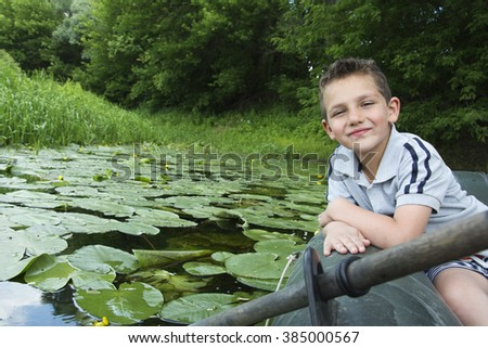 In the summer on the river curled happy boy sitting on a rubber boat. - stock photo