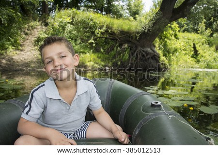 In the summer on the river curly boy sitting on a rubber boat near water lilies near a tree with huge roots. - stock photo