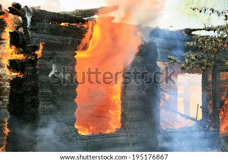In the village burning of a large wooden house - stock photo