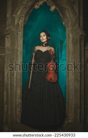 In the window there is a girl witch and smiling. In the hands of her violin. - stock photo