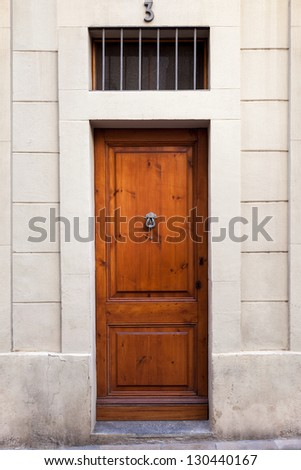 In this photograph, we can see a classic single wooden door with a knocker. The picture has been taken at the Sarri�  quarter of Barcelona (Spain). - stock photo