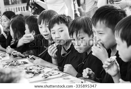 In Yen Bai, Vietnam - September 25th, 2015: Children ethnic minority people eat confectionery Tet moon on  afternoon in Yen Bai, Vietnam. Bread of love sharing of lives still lack something to eat. - stock photo