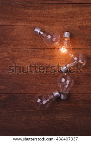 incandescent lamps and copy space on wooden background. Concept for idea. Concept for leadership. Concept for energy. - stock photo