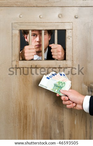 Incarcerated white collar criminal, clutching the bars of a cell door, with a hand holding a substantial amount of cash as bribe - stock photo