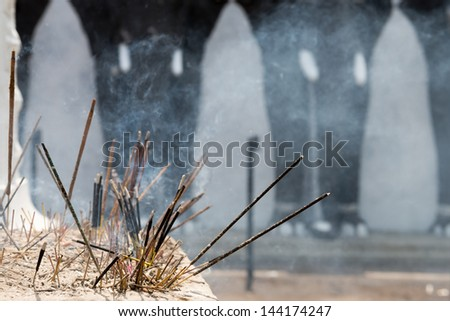 Incense sticks in a Buddhist temple with elephants on background - stock photo