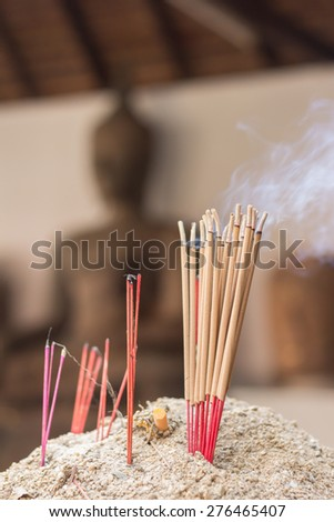 Incense sticks with blur statue - stock photo
