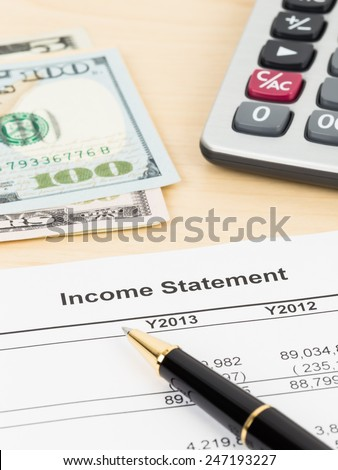 Income statement  financial report with pen, banknote, and calculator - stock photo