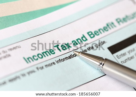 Income tax form and pen - stock photo