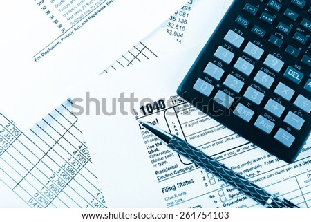 income tax return with pen and calculator - stock photo