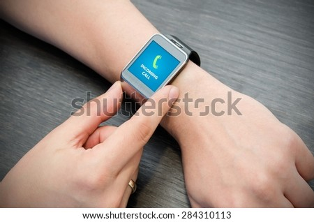 Incoming call notification on smart watch connected to smart phone - stock photo