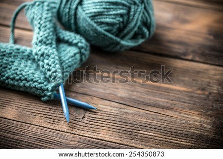 Incomplete knitting project with ball of blue wool - stock photo