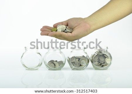 Increasing numbers of coins and hand putting coin into three glass jars . Selective focus - stock photo