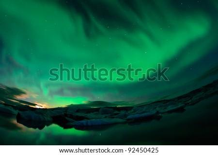 Incredible bright northern lights dancing above the floating icebergs of Jokulsarlon lagoon during setting Moon. - stock photo