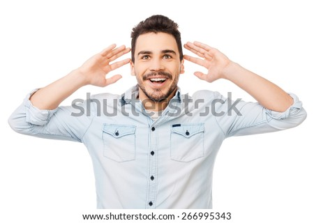 Incredible news. Portrait of surprised young man in shirt smiling while standing against white background - stock photo