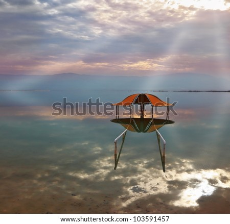 Incredible optical effects at the Dead Sea. The picturesque beach arbor for swimmers is reflected in a smooth sea surface. - stock photo