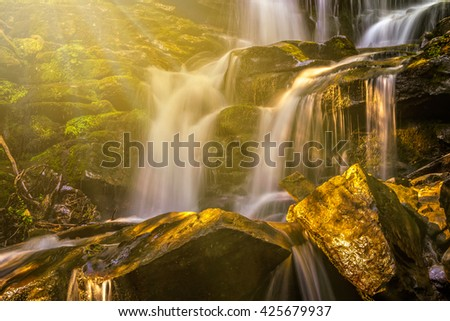 incredibly beautiful and clean little waterfall with several cascades over large stones in the forest comes out of a huge rock covered with moss in rays of morning sun - stock photo