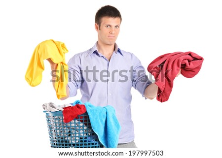 Indecisive man holding two sweaters isolated on white background - stock photo