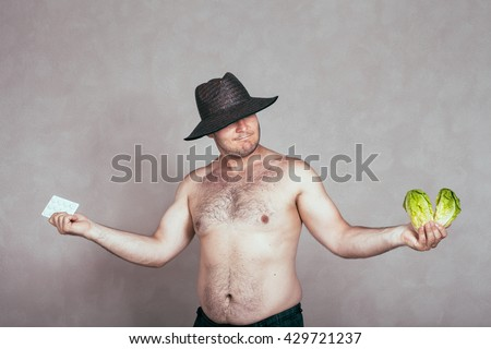 Indecisive naked corpulent man in hat holding pharmaceutical products and lettuce. - stock photo