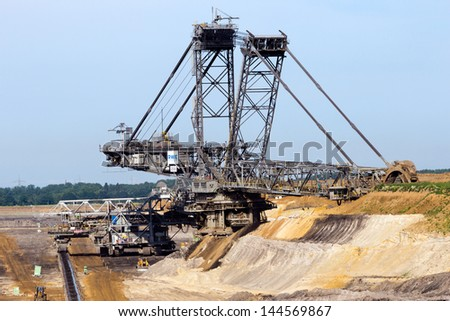 INDEN, GERMANY - JUNE 20, 2013: Large excavator digging for brown-coal in the open-pit mine at Inden on June 20, 2013. The excavation will go on till 2030, by then the area will be a big lake. - stock photo