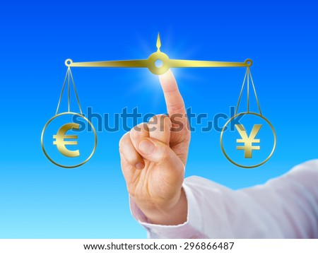 Index finger of a white collar worker is equating the European Union currency sign at par with the Japanese yen symbol on a virtual golden scale over light blue background. Financial metaphor. - stock photo