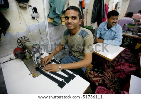 INDIA - FEB 26: Textile workers in a small factory in Old Delh on February 26, 2008 in Delhi, India. Many small factories provide the West with their clothes. - stock photo