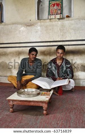 India, Rajasthan, Jaipur, two indian boys read a religious book in an hindu temple near Sisodia Rani Ka Bagh Palace - stock photo