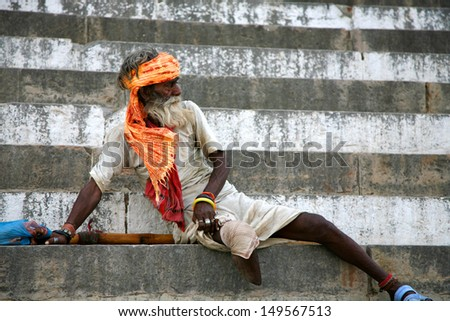 INDIA,VARANASI, MAY 30: unidentified one-legged old Sadhu standing up on the stairs of a ghat in Varanasi, poverty is a massive problem in India with big differences between social classes. 2013. - stock photo