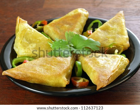 Indian appetizer: vegetarian samosas with coriander leaves - stock photo