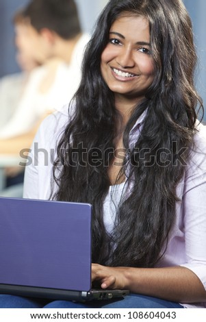 Indian Asian female student using laptop computer at college - stock photo