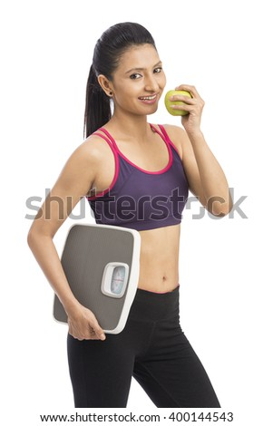 Indian attractive healthy diet eating woman with weighing scale and apple for weightloss - stock photo