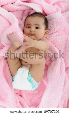Indian baby busy in playing with legs. - stock photo
